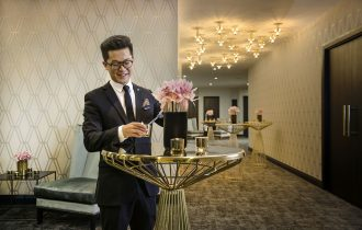 Host sets flowers up at the front desk of the Grand Mercure's conference room.