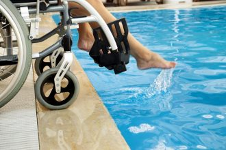 Person sitting in a wheelchair dipping their feet in a pool.