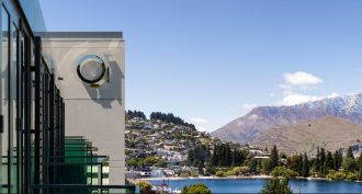 QT Queenstown exterior with exquisite mountain ranges in the background.