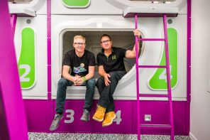 Jucy Snooze founders sitting on a pod.