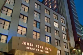 Exterior of the James Cook Hotel at night.