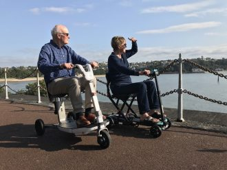 Elderly couple ride along the waterfront in mobility scooters.