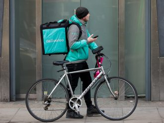 Deliveroo delivery man looks beside a hotel room elevator.