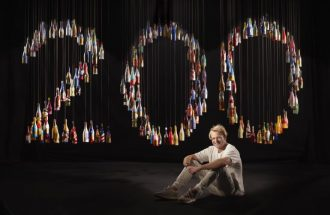 Artist Alexander Hall sits in front of his art installation.