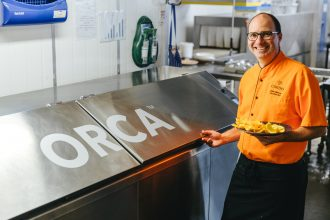 Chef Volker stands beside Orca