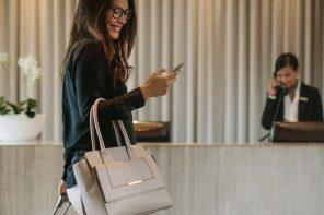 Woman using mobile phone at a lobby.