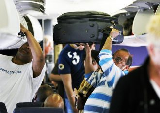 Man stows luggage on plane