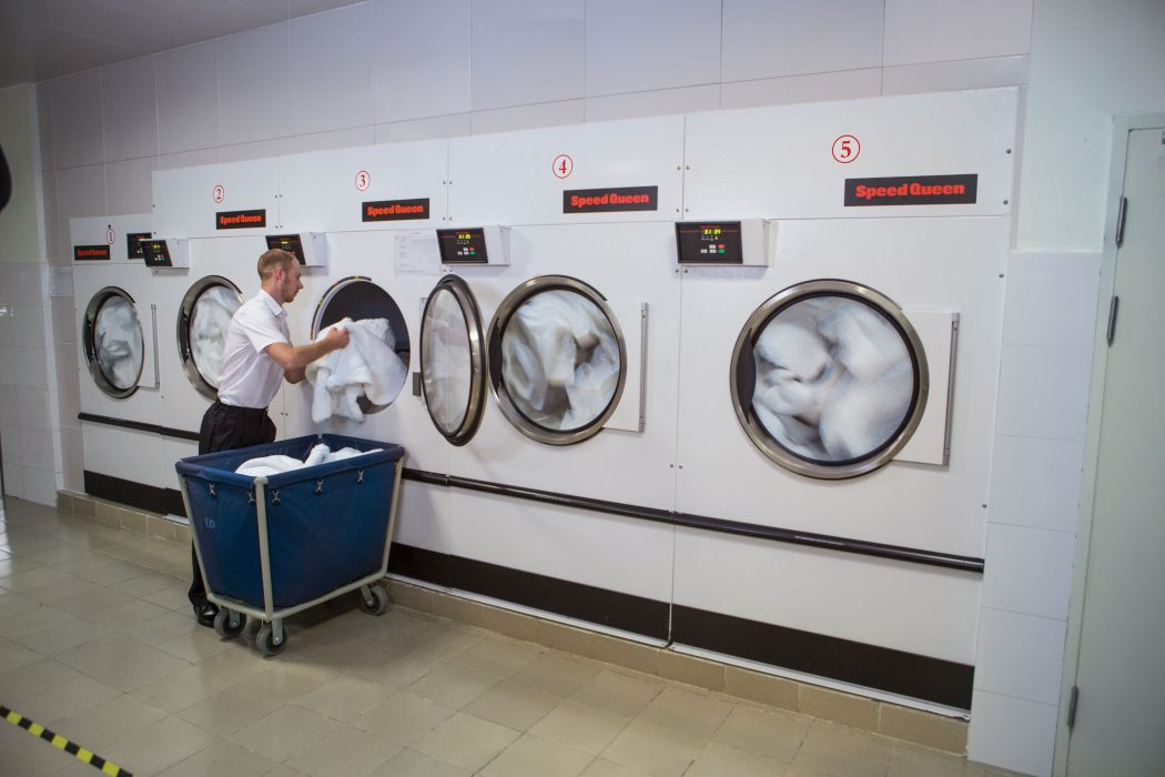 Staff putting clothes in a laundry system.