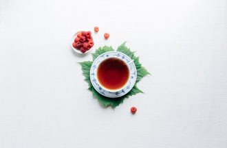 A cup of tea sits on a leaf with a white background