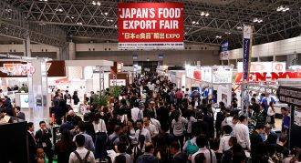 A busy trade expo centre with a sign hanging above which reads 'Japan's Food Export Fair''