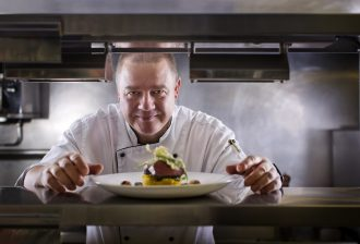 Chef Jorg Penneke looks through the pass with a meat dish in the foreground