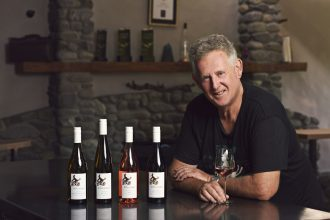 Dr John Forrest with four bottles of his eponymous wines