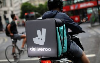 A deliveroo rider prepares to enter traffic