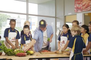 A group of school children watch Al Brown prepare a meal