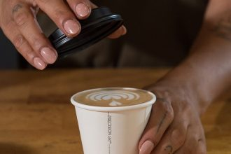 Hand places lid on a Detpak Precision Series takeaway coffee cup