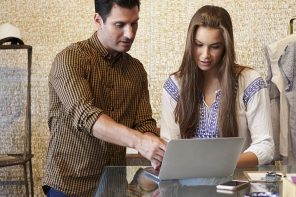Man demonstrates girl PAYE on a laptop.
