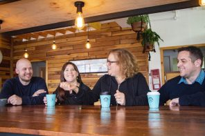 a group in a cafe drinking coffees from idealcups used in the cupcycling scheme. they're light blue