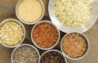 Ancient grains and healthy organic edible seeds in round stainless steel containers. These are considered superfoods.