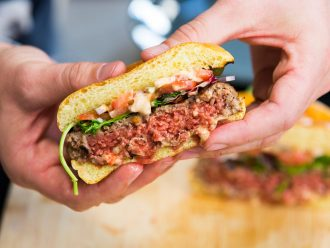 Impossible Meat burger 2.0 cut in half and held by two hands
