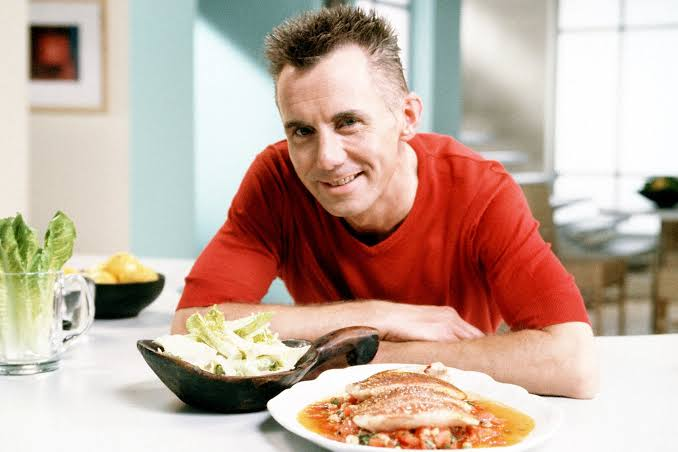 Gary Rhodes smiling at camera with plate of food in front of him