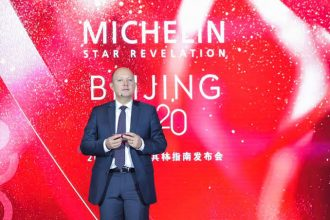 Man in a grey suit standing infront of red screen with text saying michelin