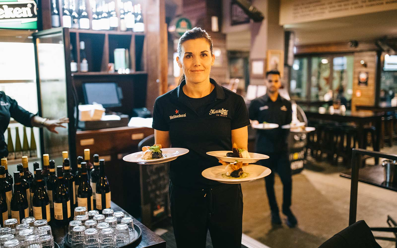 Female waiter looking at camera holding three plates of food