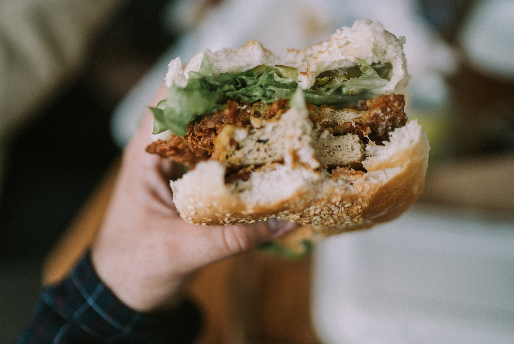 Plant-based chicken with bites held up by hand
