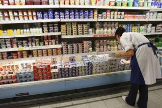 someone leaning over a refrigerated section, performing a safety check on products