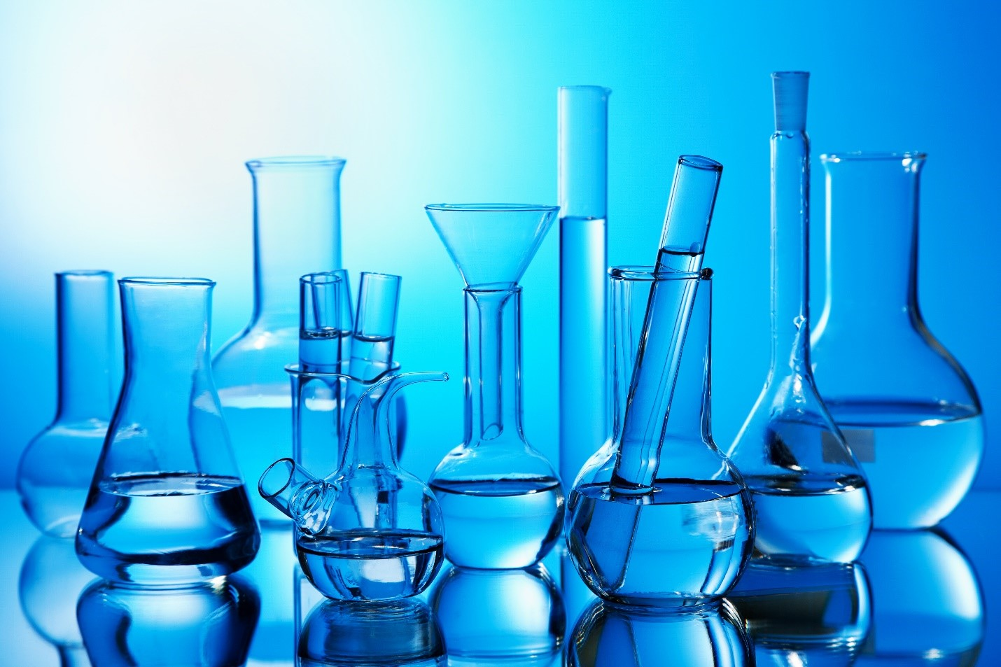 clear beakers with clear liquid in them against a blue background. very clinical vibe