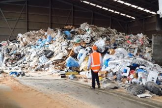 a lone waste management worker walks toward a pile of plastic waste
