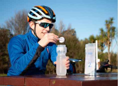a cyclist pours PowerAmp's Rapid Hydration sachet into his water bottle