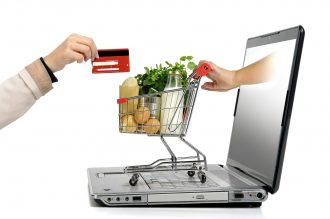 Hand with credit card and a small shopping cart coming from laptop screen isolated in white