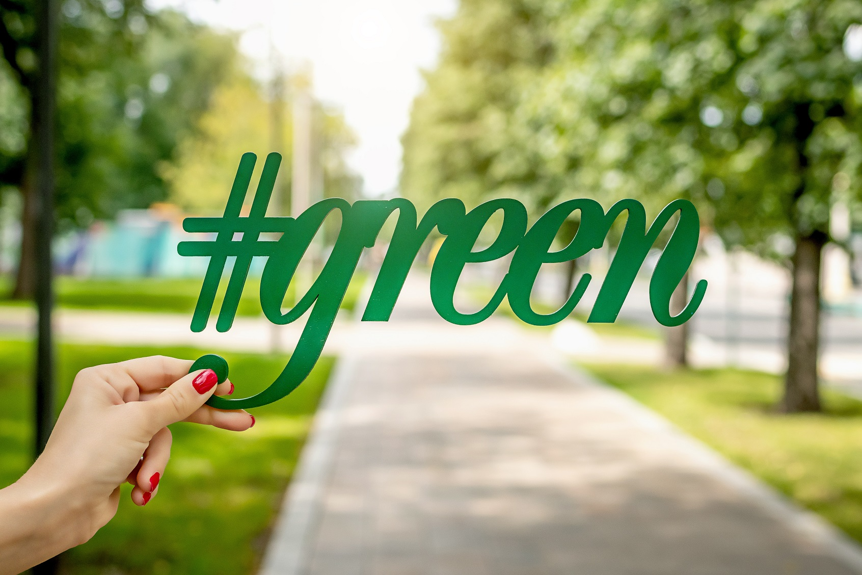 Lady's hand holding text that says #green