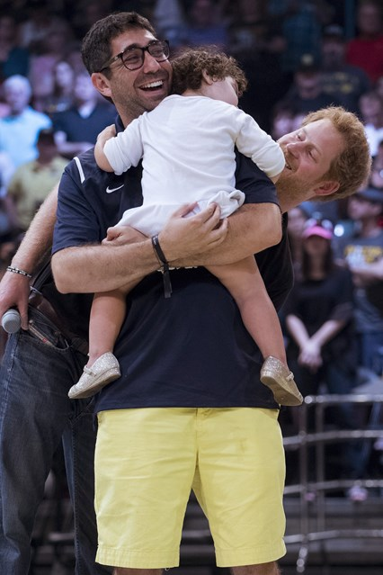Prince Harry is shown to be playing with a young attendee at the Invictus Games in Orlando.