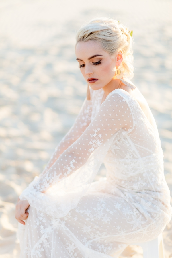 erin clare bridal. model wears beautiful white wedding gowns on a beach