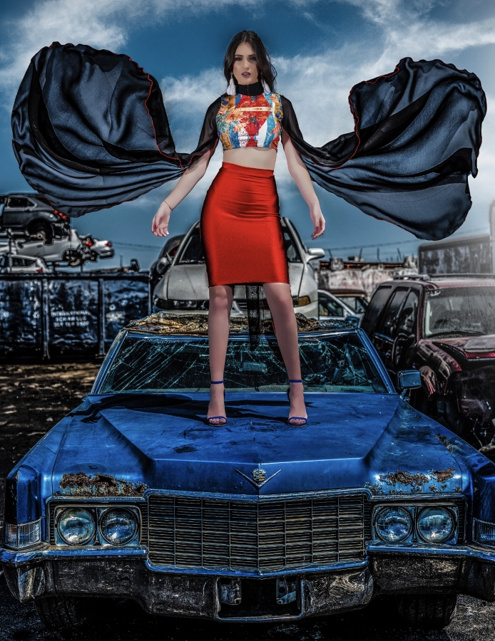 yas gonzalez fashion shoot. a model stands on a blue car, a cape flying out on the wind