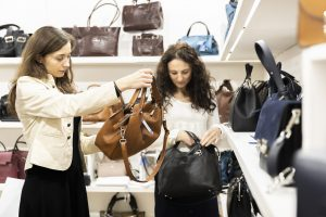 Two women looking at a leather bag each in a store