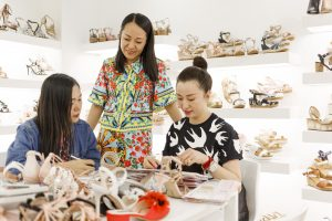 Three women looking at a selection of shoe samples in a store