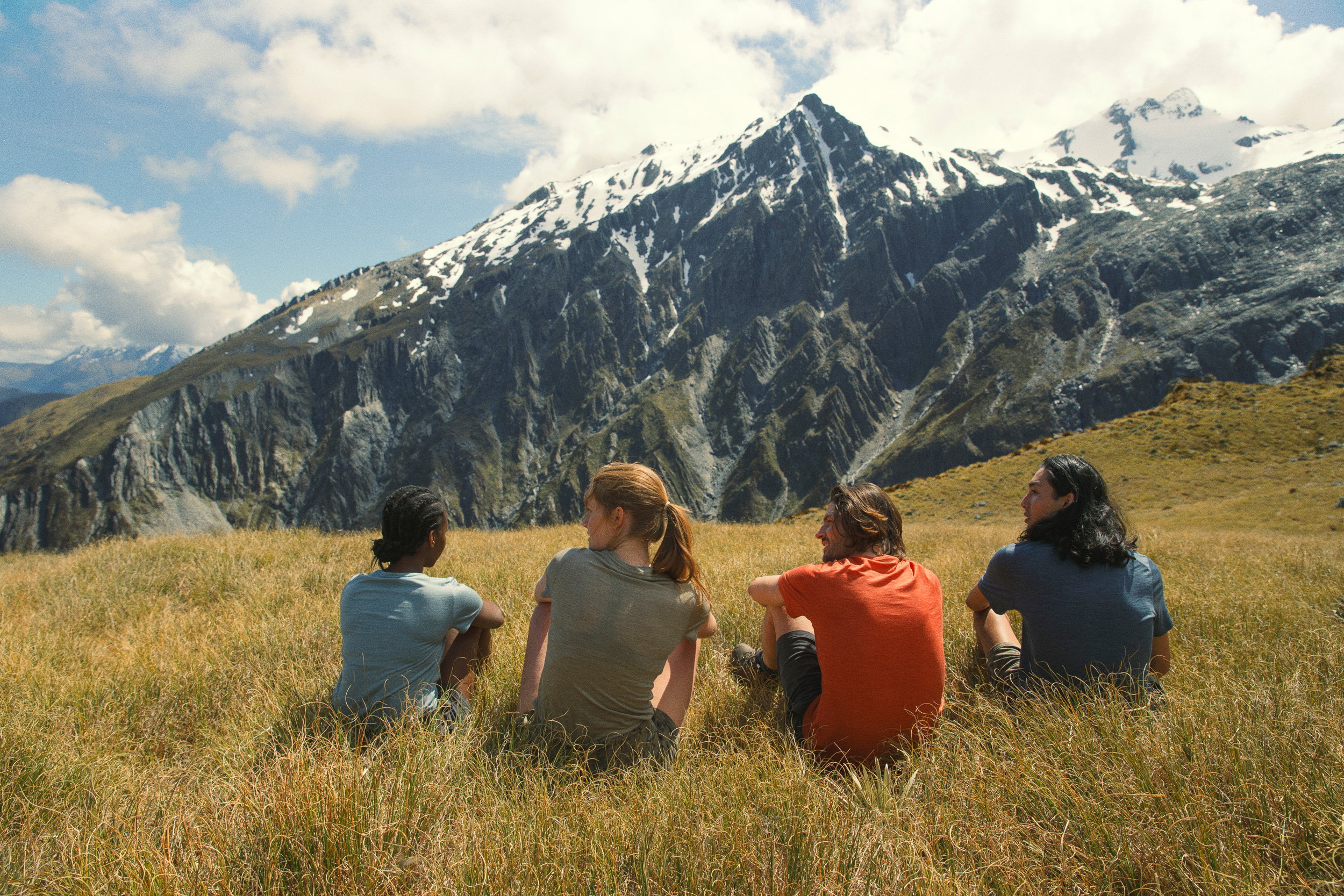 4 people sitting facing mountain away from the camera